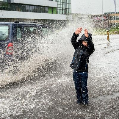 <strong>Regen water douche</strong><br><p>Een jongetje laat zich nat rijden na een hevige regenbui - Drachten</p>